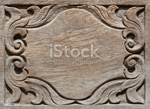 Old weathered wood board background, with carved ornate corners.