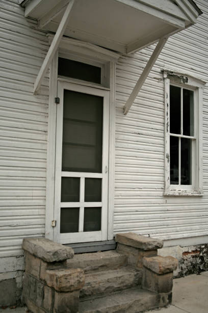 Old weathered wooden house with porch entrance, peeling paint, & dirty windows stock photo