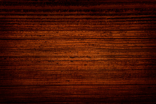 Weathered dark reds wood background. The old board has a clear texture of wood. Scratches, cracks and other damages are strongly expressed. A wood grain pattern featuring even grains of wood running horizontally across the image. Lines of annual rings are unequally distributed.