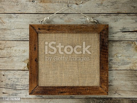 Old weathered worn natural wooden picture frame with burlap sac material framed in it, hanging from a hook on an old worn weathered wood panel wall background. The frame is very rustic with lots of weathering and detail etc.