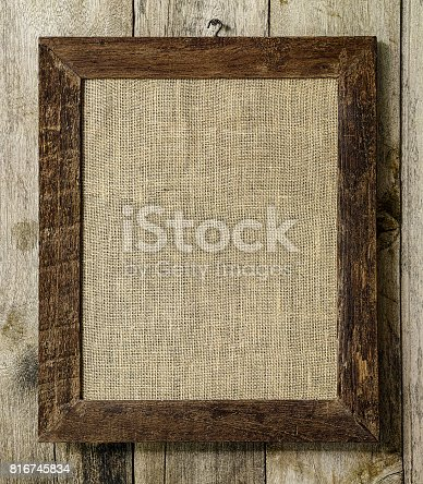 Old weathered worn natural wooden picture frame with burlap sac background framed in it, on an old worn weathered wood panel wall background. The frame is very rustic with lots of weathering, rustic detail etc.