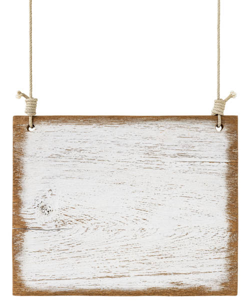 Old weathered worn white wooden board sign panel, hanging by old rope, isolated on white, clipping path included. stock photo