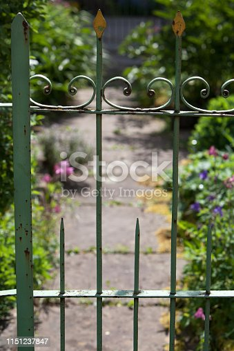 Old weathered wrought iron garden fence with a garden path in the baclground