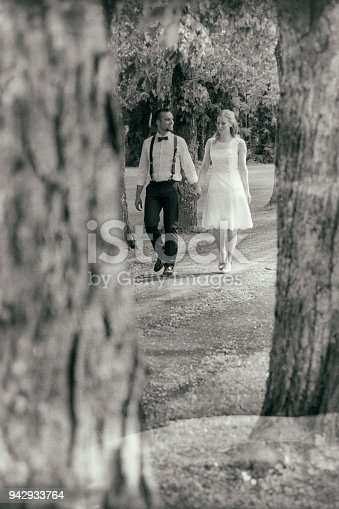 Wedding couple walking through tree-lined street.