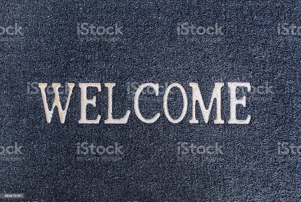 Old welcome doormat close up stock photo