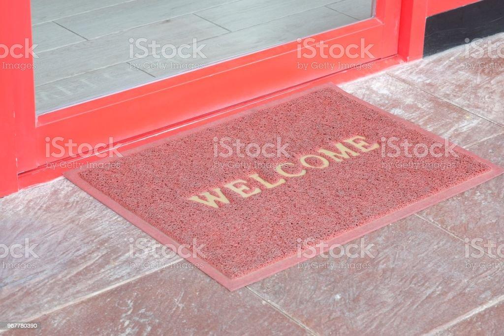 old welcome text on red doormat in front of door