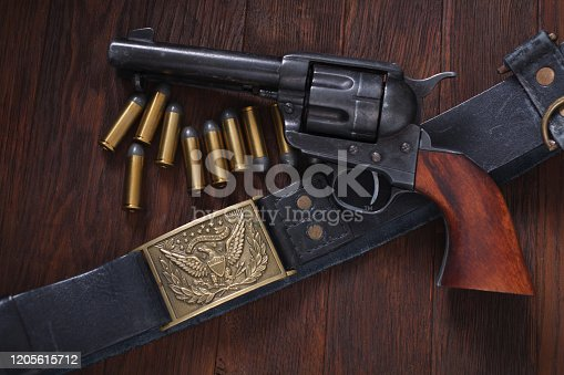 Old western revolver with cartridges on wooden table