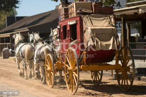 Antique stagecoach travelling down an old western street.