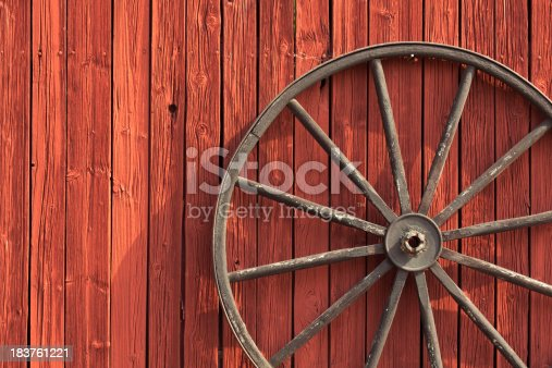 Old wheel on barn wall.