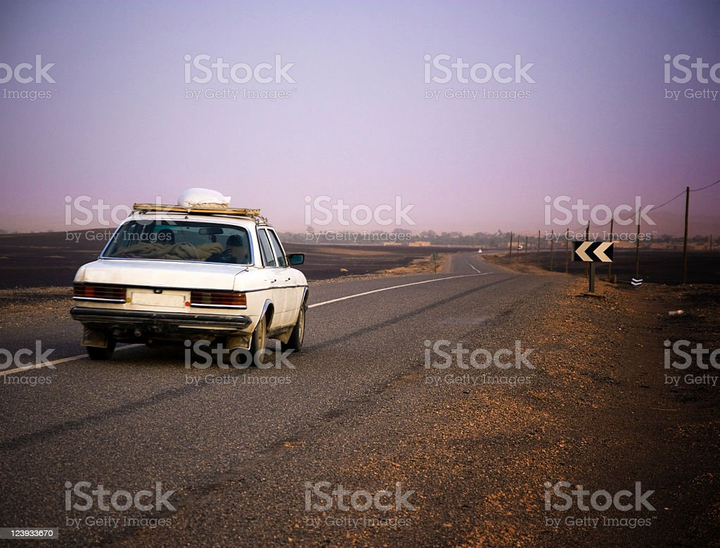 Old White Car Driving in the Desert At Sunset royalty-free stock photo