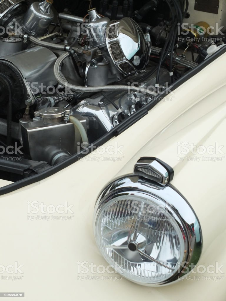old white car with the engine visible though open hood with headlamp alternator and air filter visible stock photo