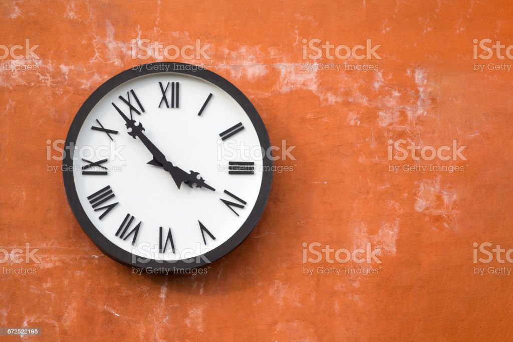 Old white clock on cement wall background with copy space. stock photo