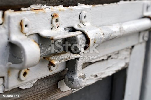 A close up image of an old white door latch.