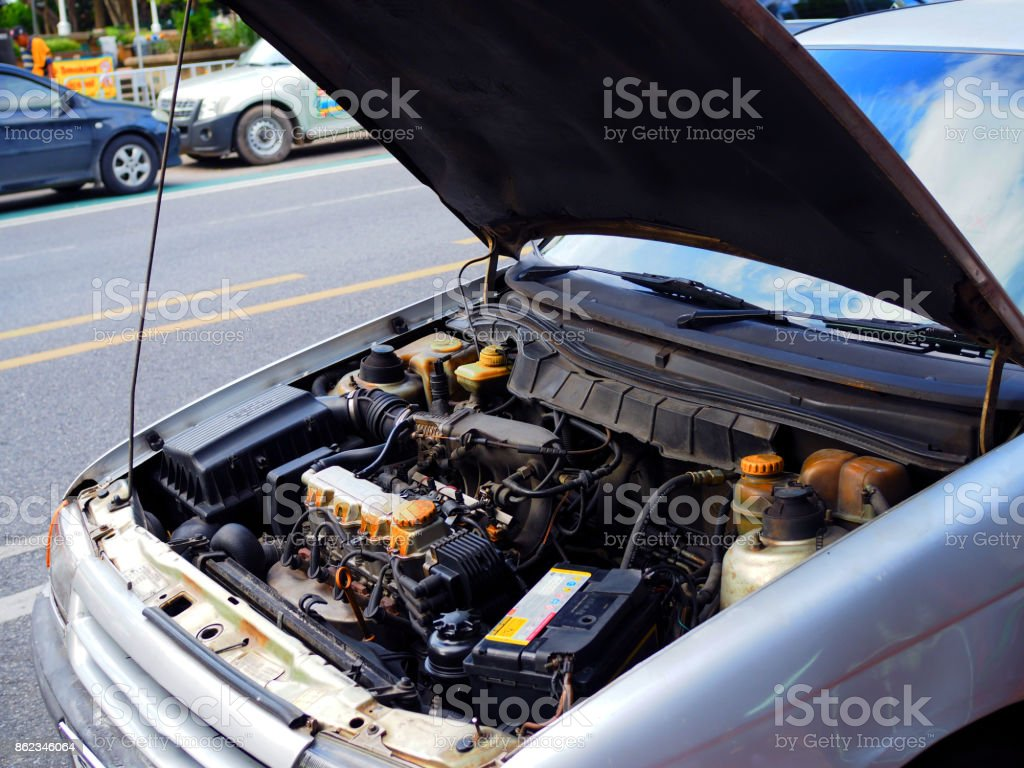 Old white grey car engine, hood opening, beside the street stock photo