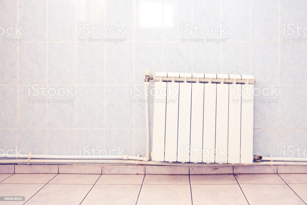 Old white heating radiator on tiled wall with pipes stock photo