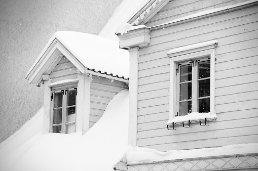 Old white house with two windows under snow