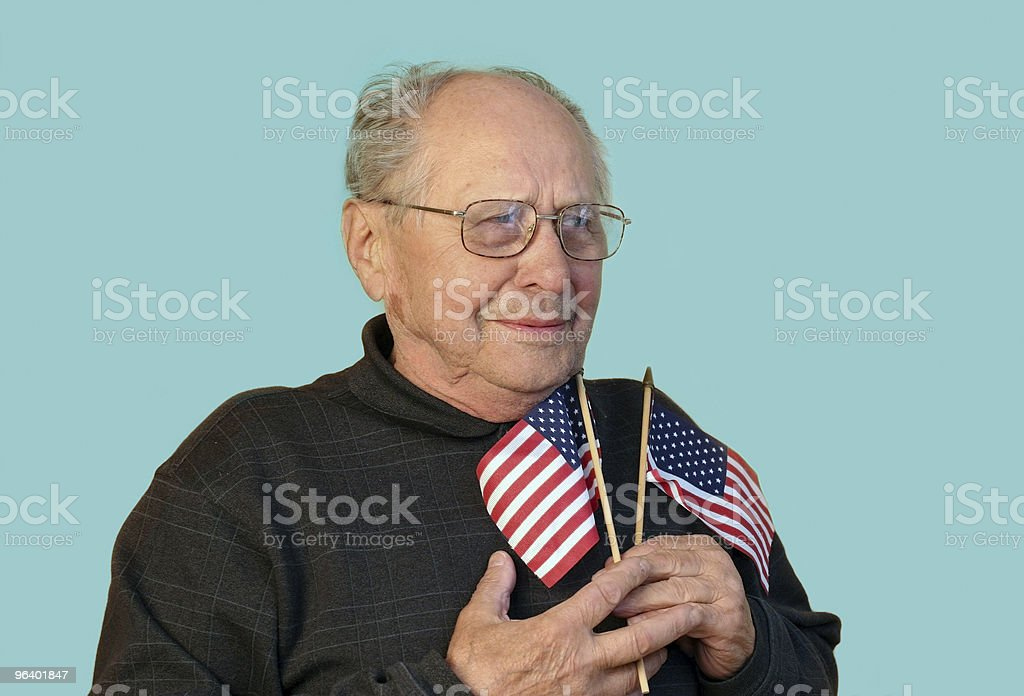 Old white man with two American flags on teal background  royalty-free stock photo