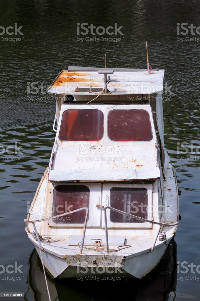 Old white river fishing boat parked at lake river / Motor Boat parked around bank of river. stock photo