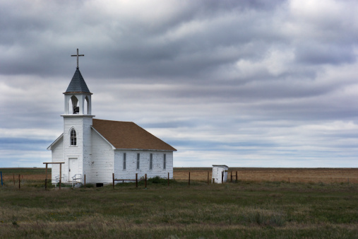Horizontal view of a lonely rural church by a prairie farm field, under a stormy sky in western rural South Dakota, U.S.A. The old white wooden built structure has a steeple with a cross and bell tower. The forbidding landscape, cloudscape and Christian symbols reflect dark simplicity and loneliness.
