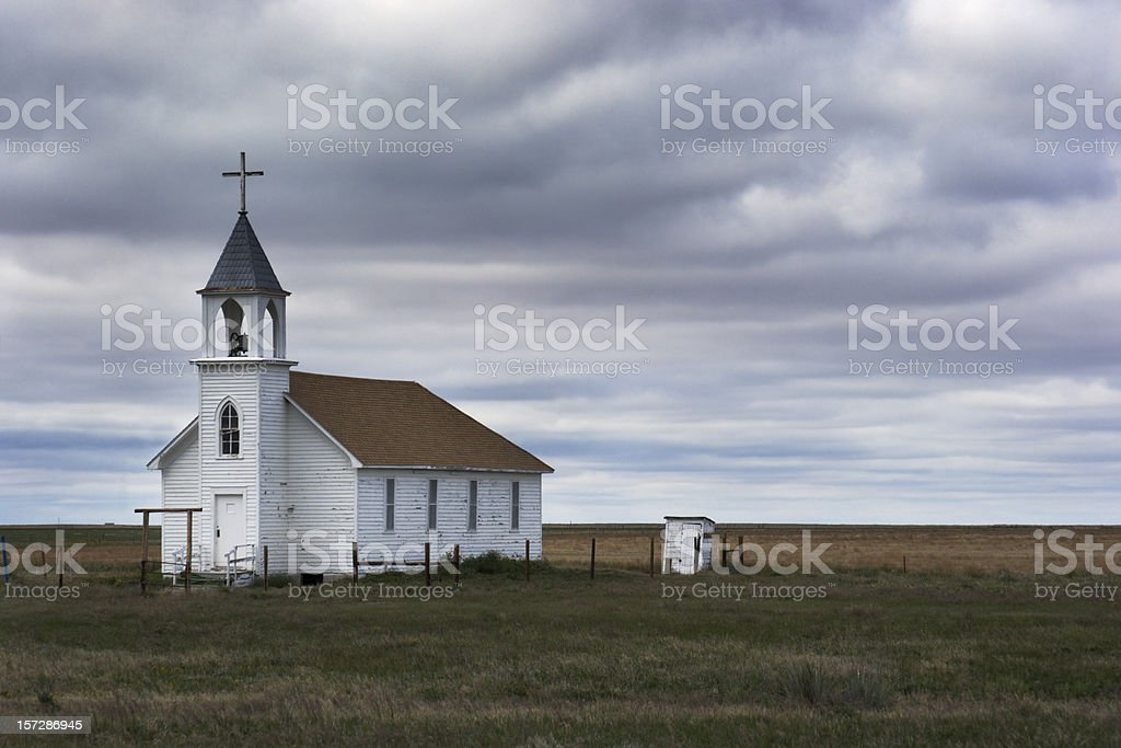 Old White Wooden Church in Rural Field Scene with Storm stock photo