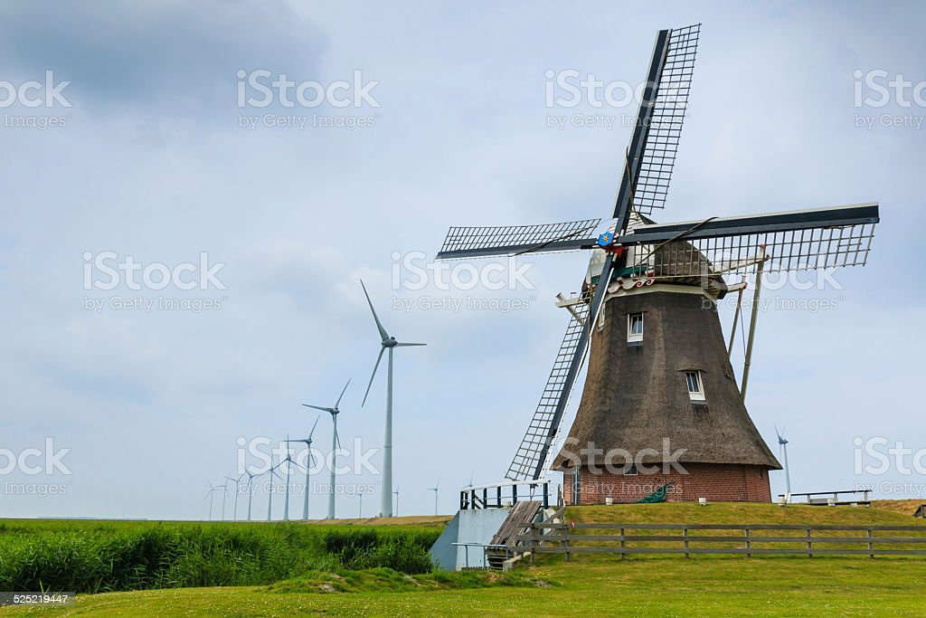 Old windmill and new wind turbines stock photo