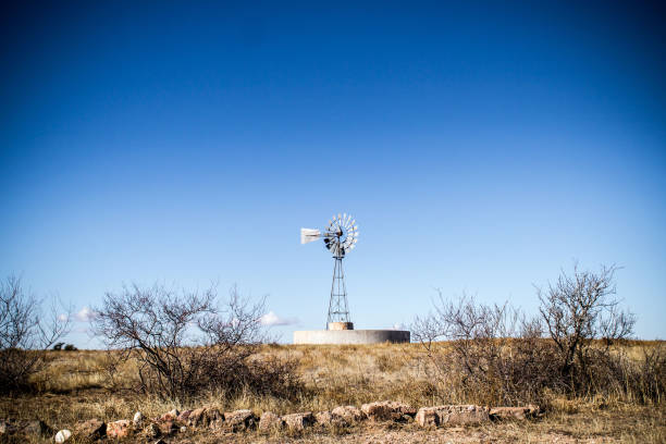 Old Windmill In Desert In Clear Sky stock photo