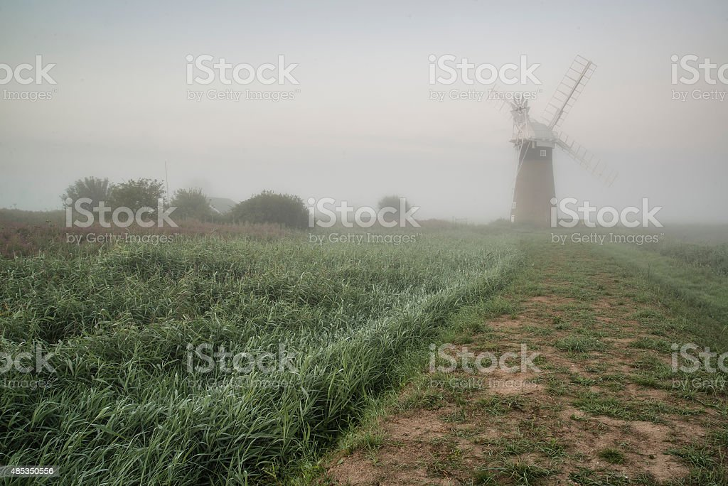 Old windmill in foggy countryside landscape in England stock photo