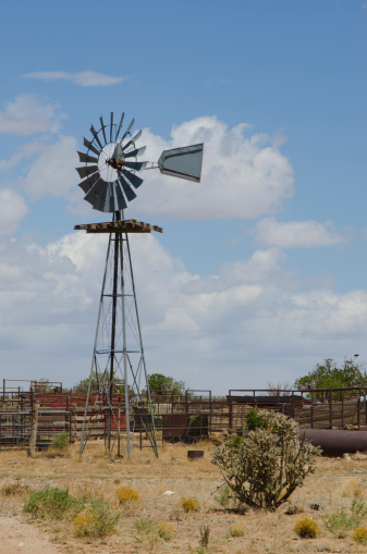 An old windmill on a cattle ranch is still in good operating order, as the water it brings to the surface is in great need in the desert of New Mexico.