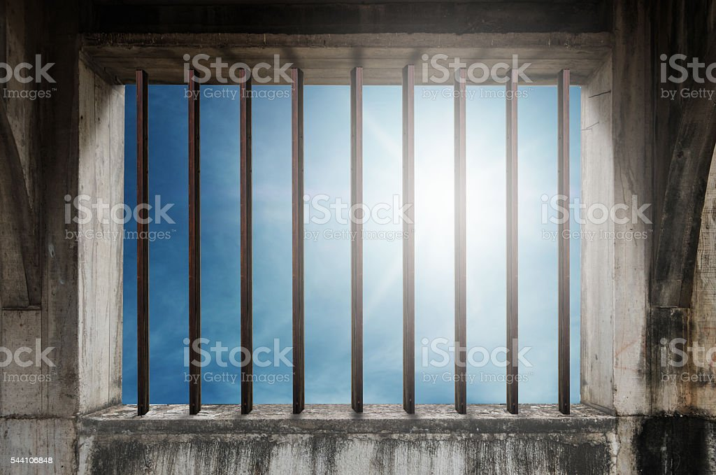 Old window frame with iron bar in jail with sky stock photo