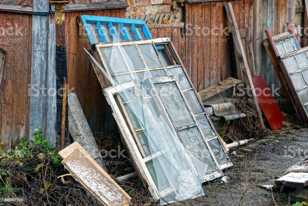 old window frames and broken glass with boards in a heap of rubbish in the street stock photo