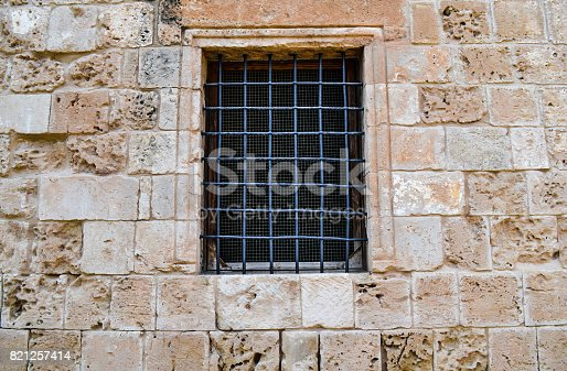 Old window in the castle wall with a lattice