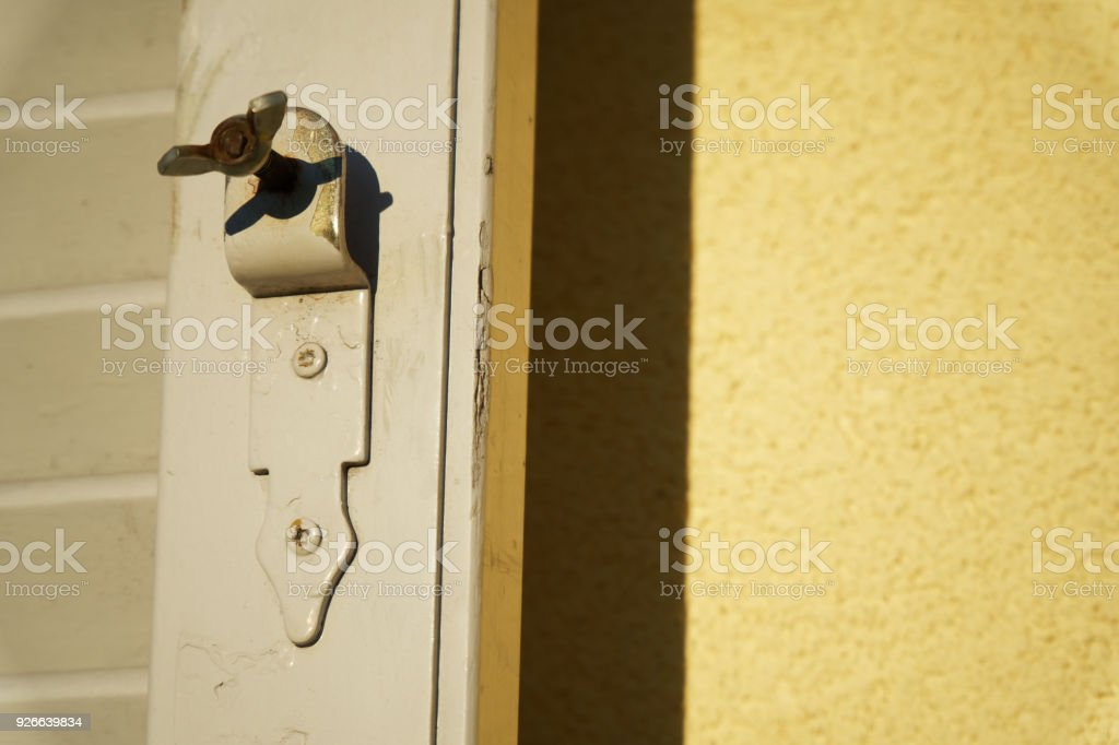 Old window latch with already worn white paint. Focused closely and with space for texts. stock photo