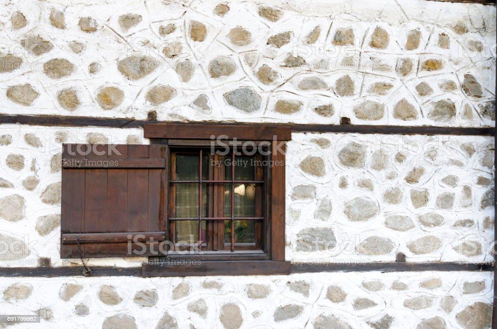 Old window on stone house in Bansko, Bulgaria stock photo