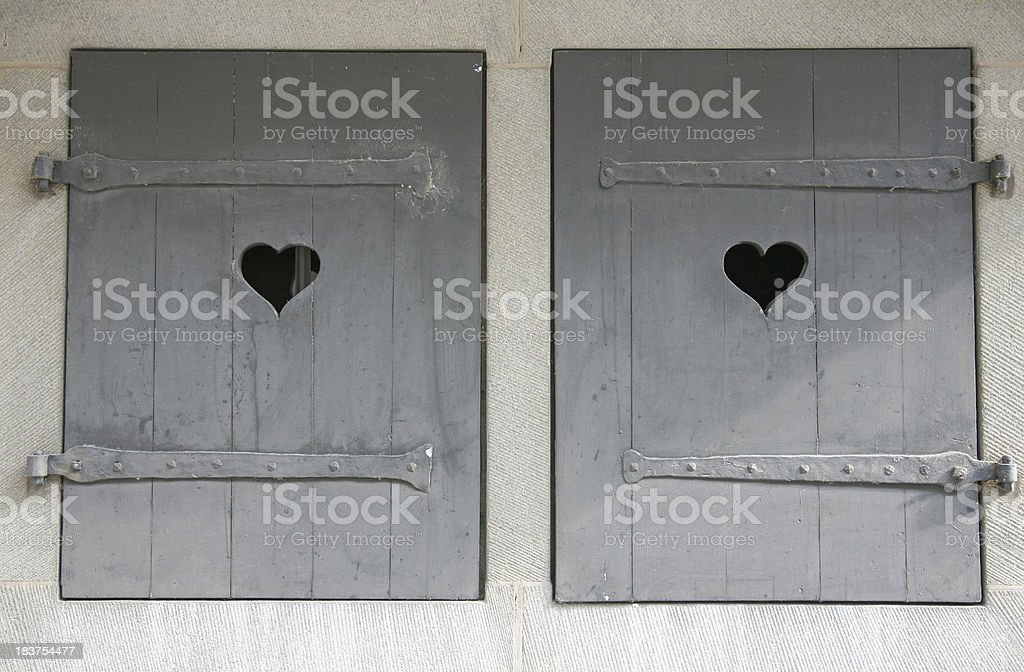 Old window shutters with heart symbols royalty-free stock photo