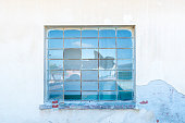 Detail of an abandoned house with broken window.
