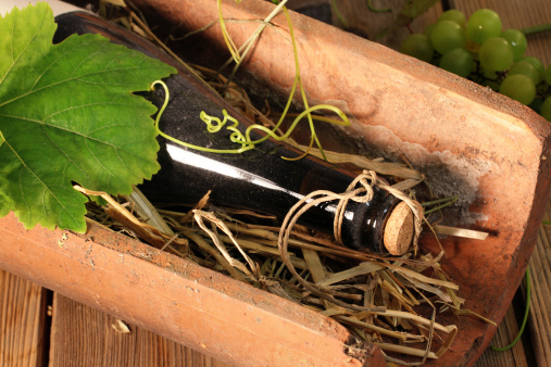 Old wine bottle on a tile with wine leaves