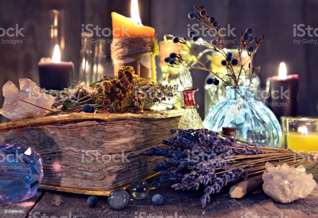 Old witch book with lavender flowers, crystal and evil candles stock photo