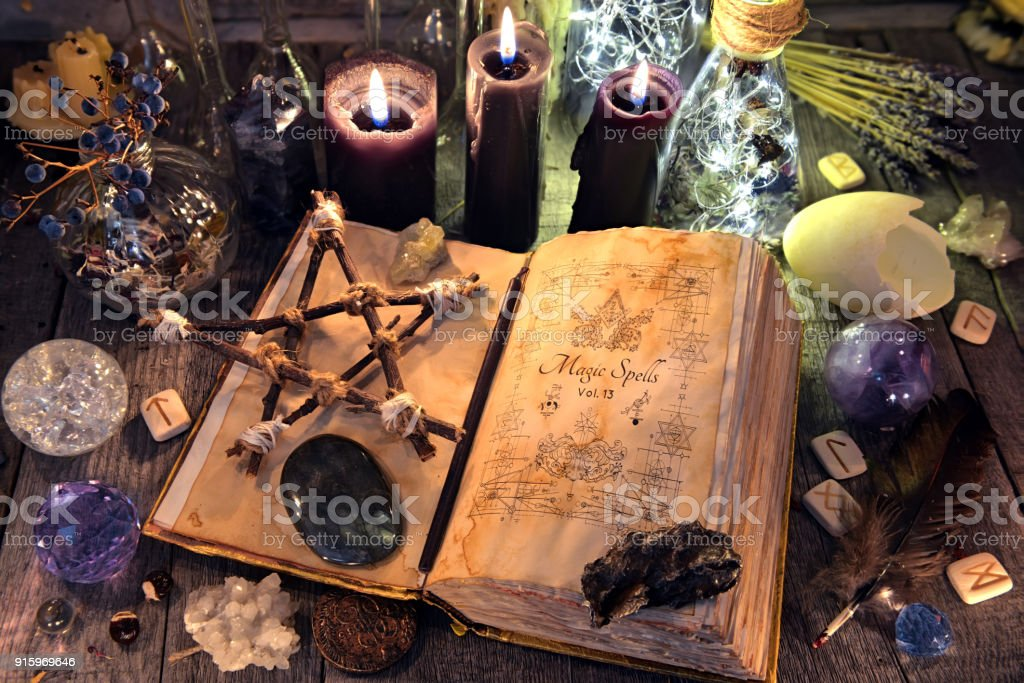 Old witch book with pentagram, black candles, crystals and ritual objects stock photo