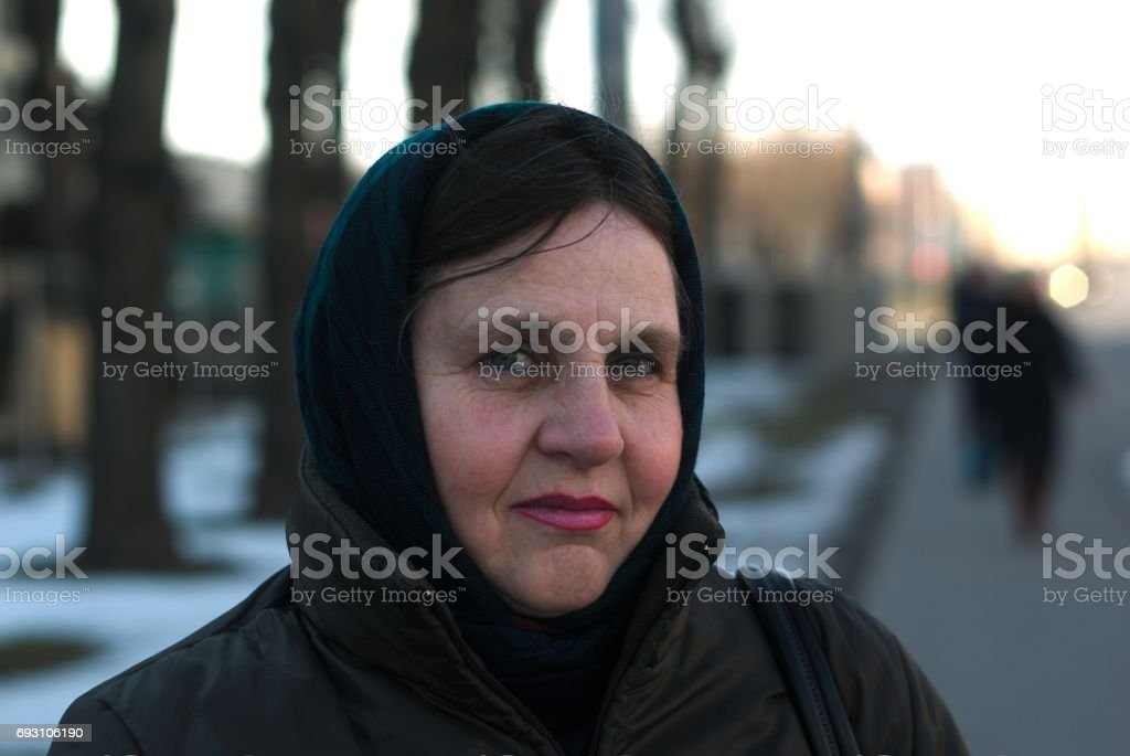 Old woman alone in a scarf portrait. stock photo