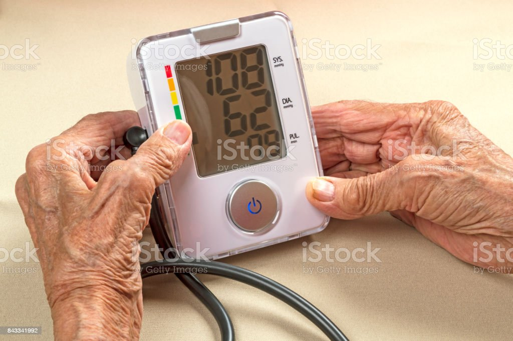Old woman and digital blood pressure monitor stock photo