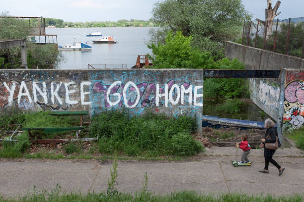 """alte frau und ihre enkelin, vorbei an einer wand mit einer anti-amerikanische inschrift an der wand: """"yankees go home"""" in belgrad, serbien - imperialismus stock-fotos und bilder"""