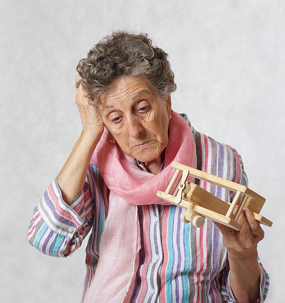 old woman and wooden made airplane. - wie lange leben fliegen stock-fotos und bilder