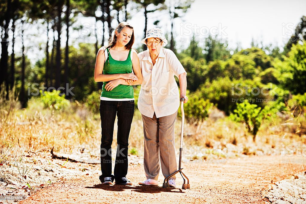 Old woman and young girl look serious on forest walk stock photo