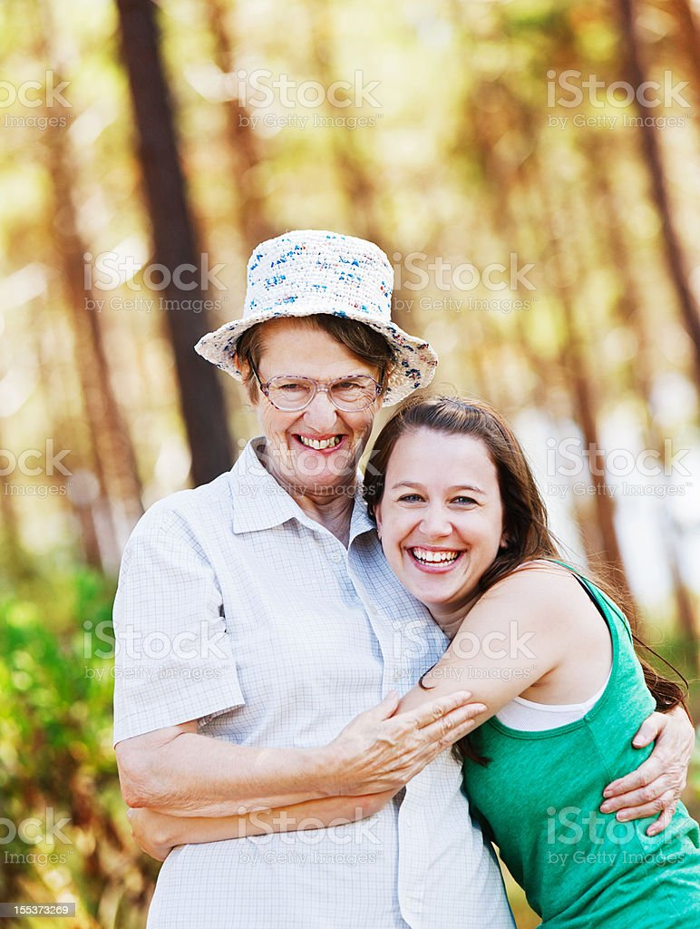 Old woman and young girl sharing a joke in forest stock photo
