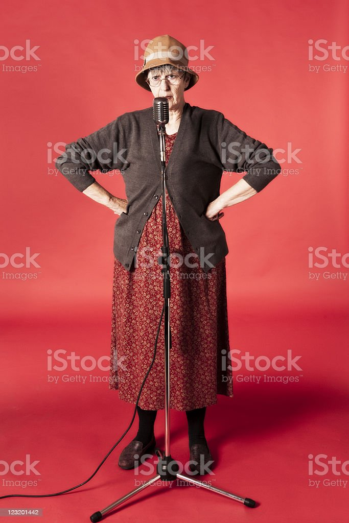 Old woman, arms akimbo, talks into retro microphone royalty-free stock photo