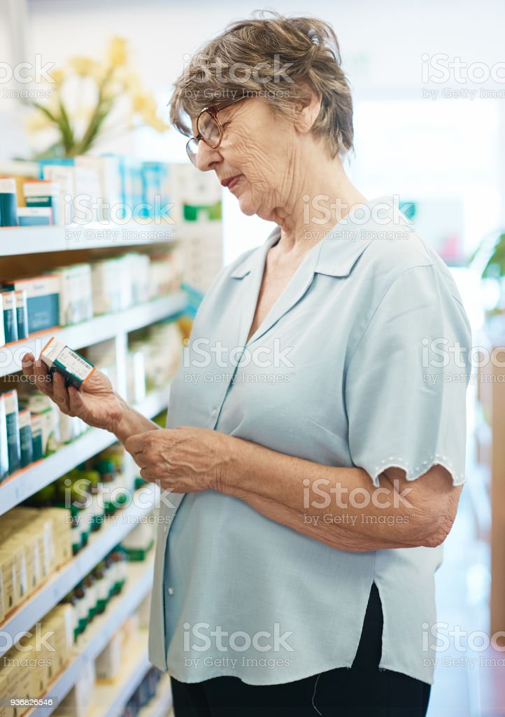 Old woman browsing the shelves at a pharmacy stock photo