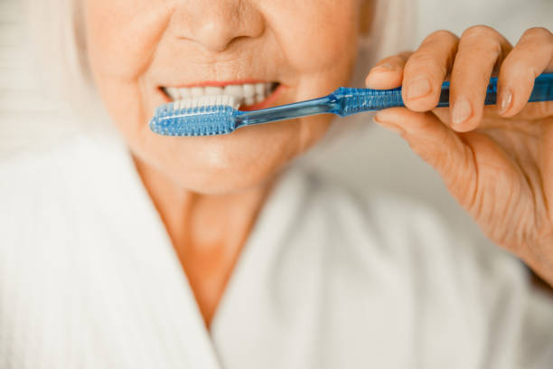 Old woman brushing teeth in the morning stock photo