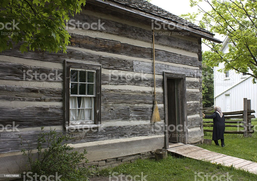 Old woman by her log cabin stock photo