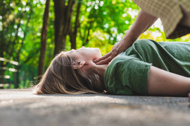 Old woman checking pulse of a young fainted girl Unconscious fainted girl having pulse checked by an old woman – Teenager lying on the ground while her pulse is verified by an elder citizen on teen's carotid artery woman taking pulse stock pictures, royalty-free photos & images
