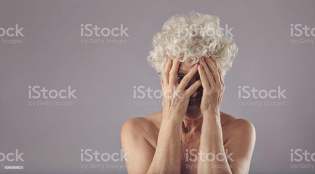 Old woman feeling shy stock photo